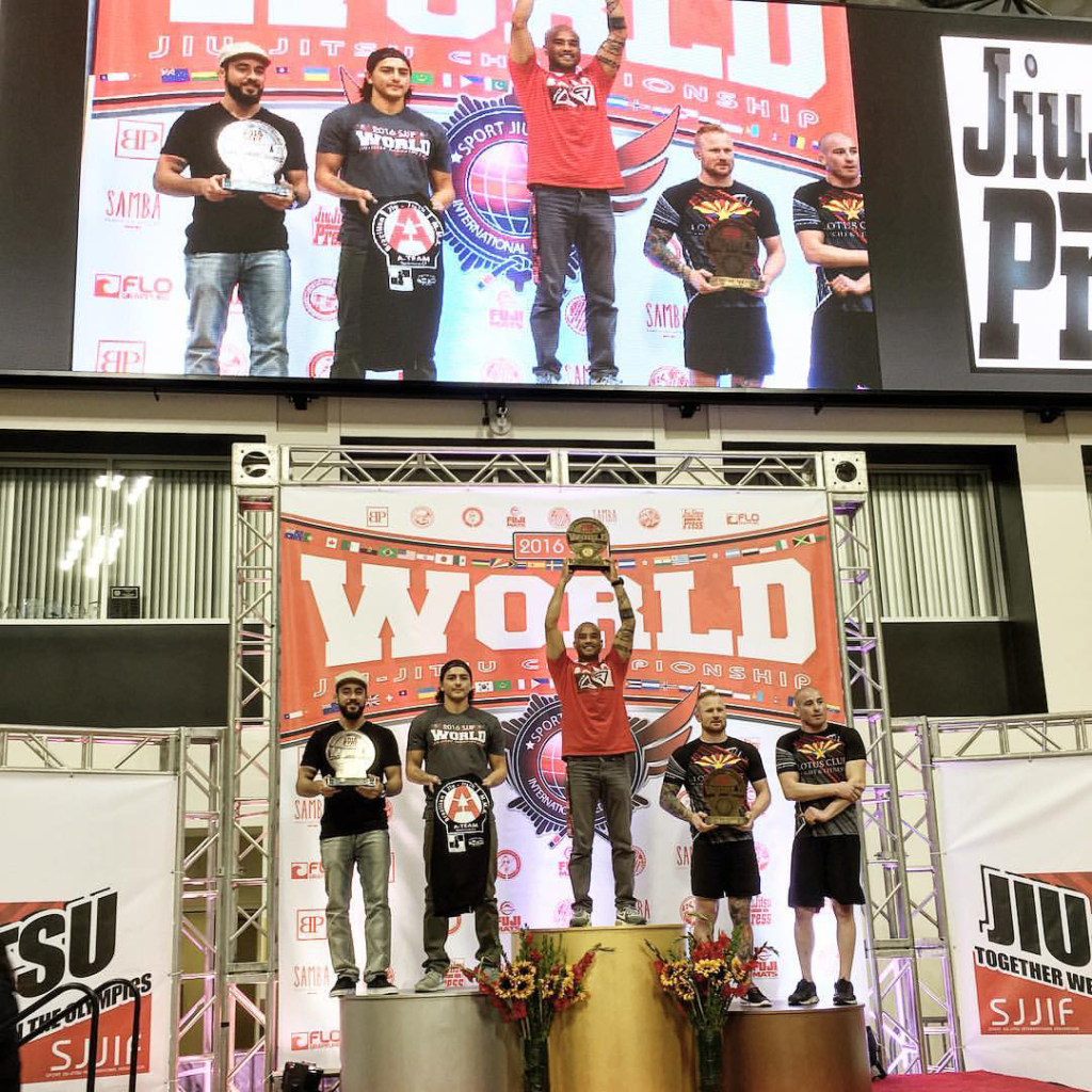 Professor Alex D'Hue on podium at the Walter Pyramid in Long Beach, holding SJJIF Kids Jiu Jitsu World Championship Trophy