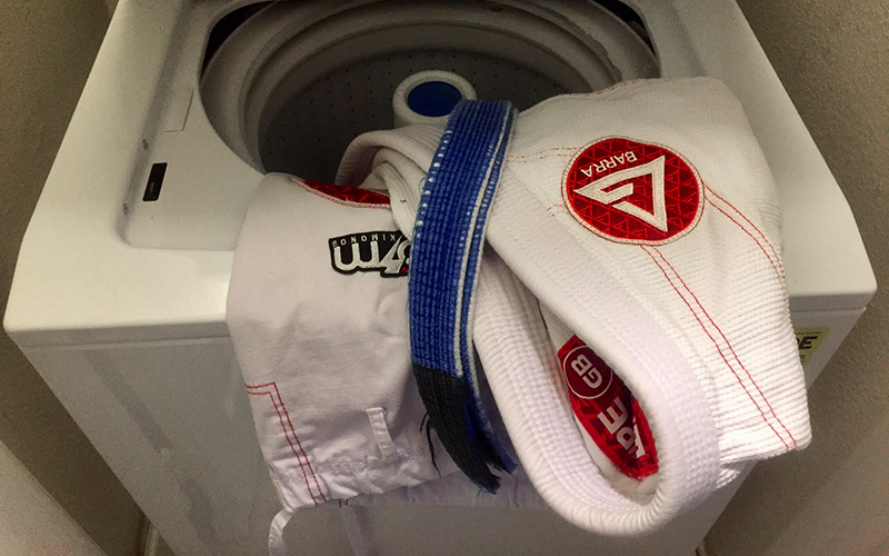 Gracie Barra Jiu Jitsu gi being placed into washing machine